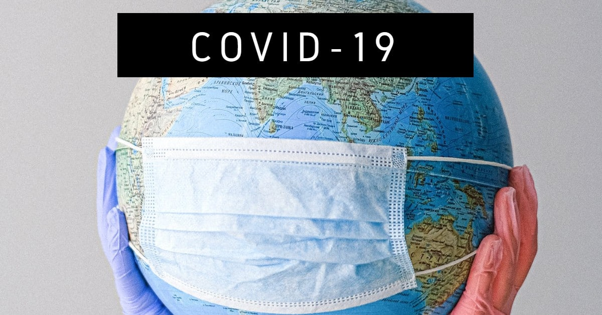 "Photo of globe with a surgical mask held up with latex gloves and the words ""covid-19"""