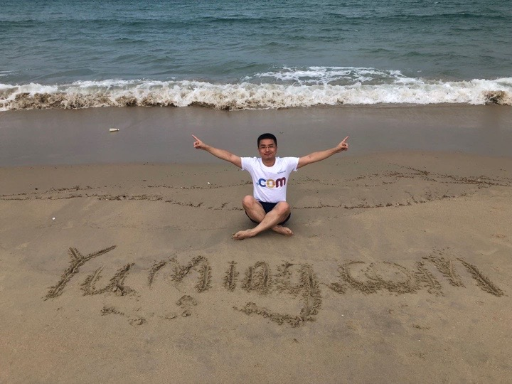 """A photo of domain name investor Yue Dai on the beach, with """"yuming.com"""" written in the sand"""