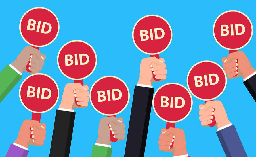 Hands holding bid cards in auction