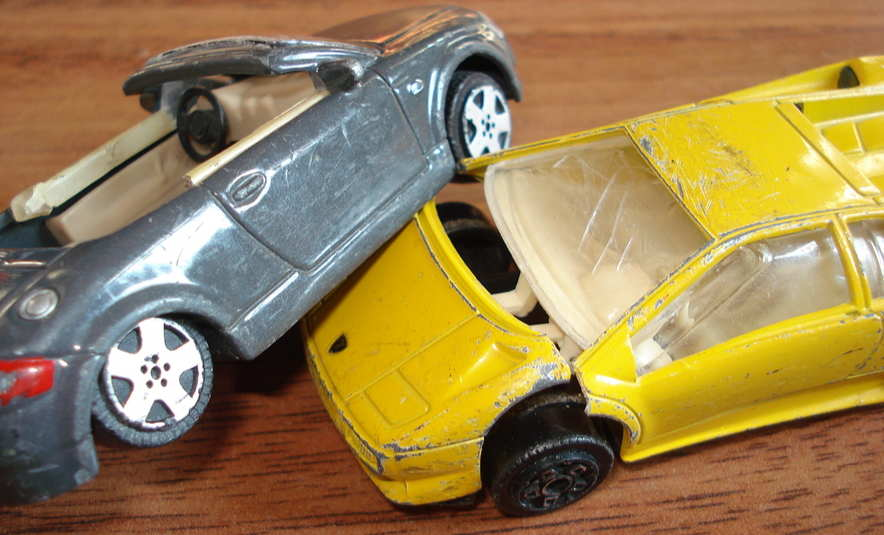 Picture of toy matchbox-style cars in a crash. Grey convertible and yellow coupe.