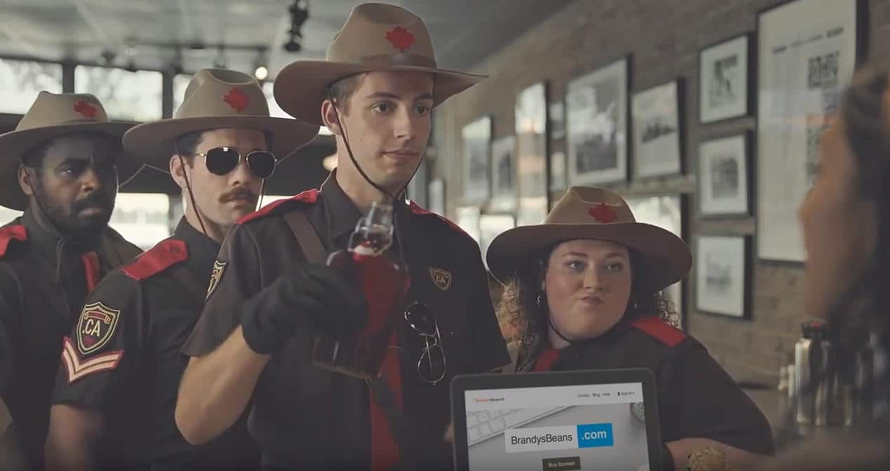 Still screen from CIRA ad for .CA domains shows four Canadian mounties with one of them pouring syrup on a person's laptop who is registering a .com domain