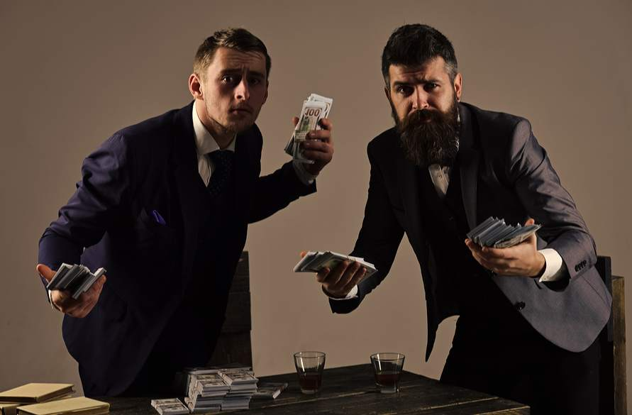 Picture of two men holding cash in secret back room