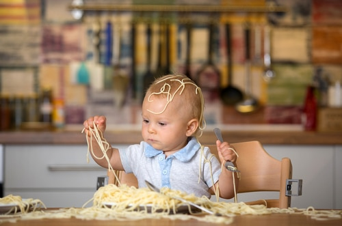 Picture of a kid making a mess with spaghetti