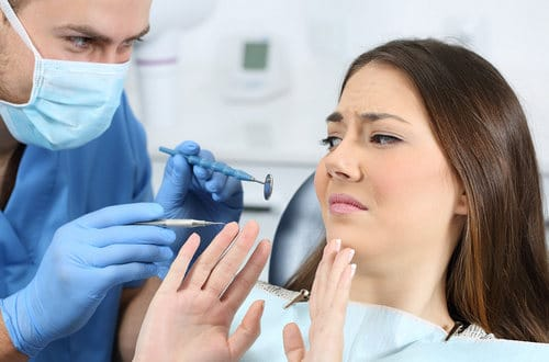 Picture of woman pushing back against dentist