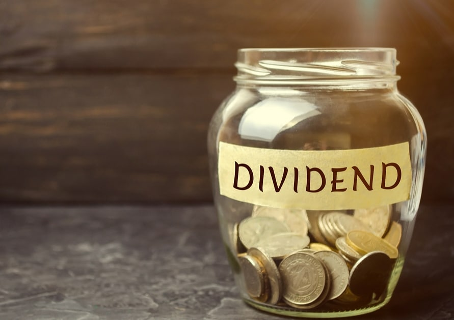 "Picture of a jar with coins in it and the word ""dividend"""