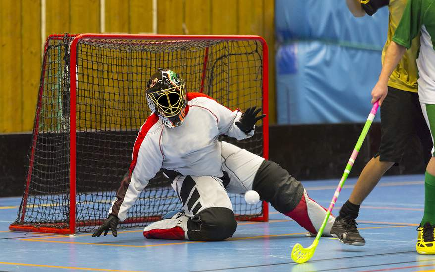 Picture of Floorball game with goalie blocking a shot