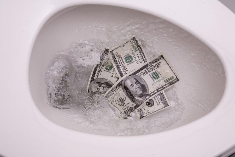 Picture of money being flushed down the toilet