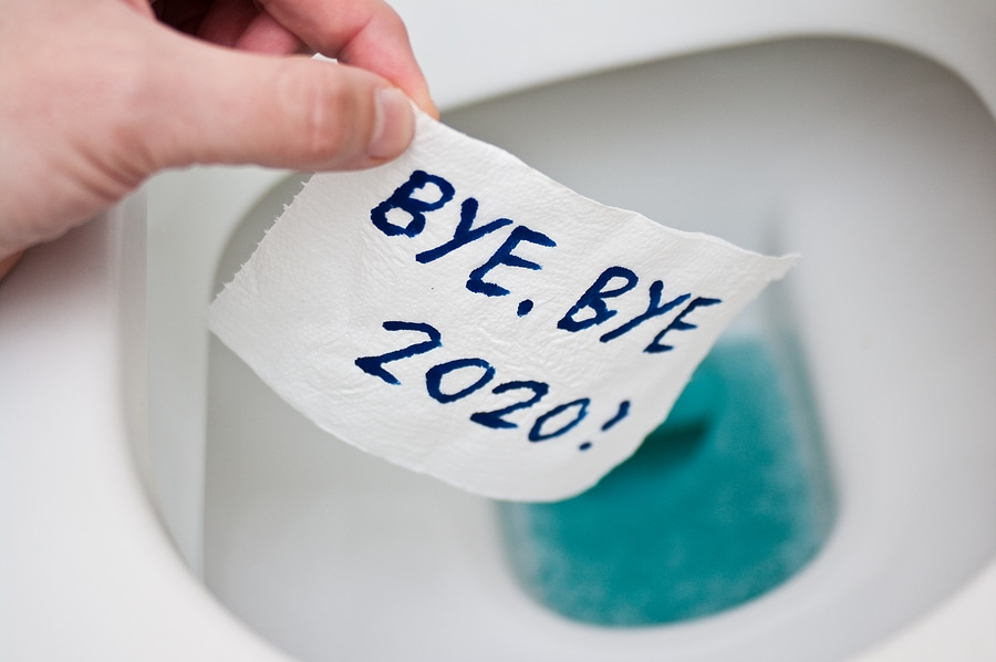 "Picture of hand dropping toilet paper sheet with ""bye, bye 2020!"" written on it into a toilet bowl"