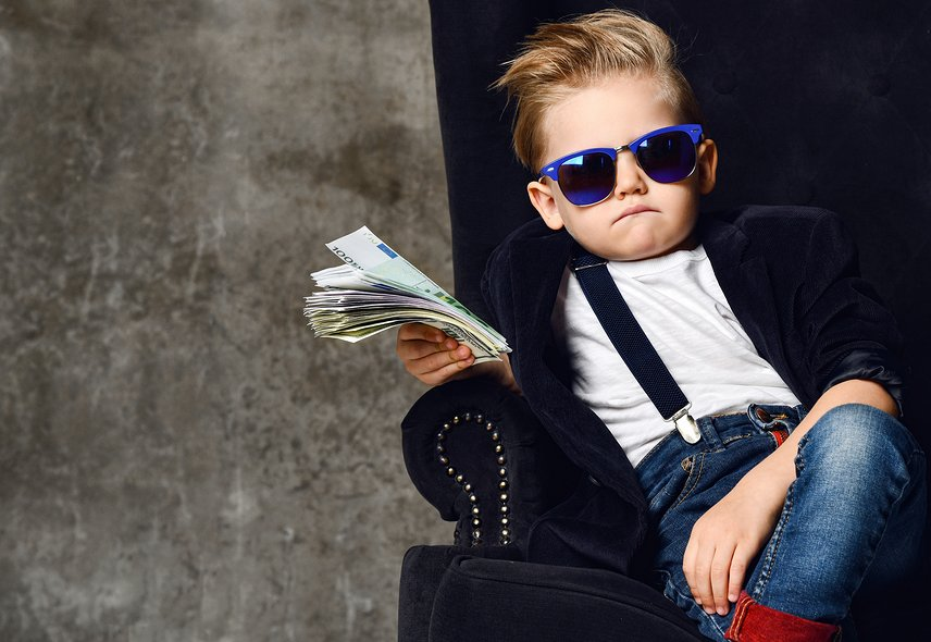 Picture of kid with sunglasses and suspenders sitting in black chair holding money