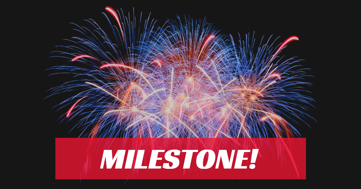 """Picture of red, blue and yellow fireworks with the word """"milestone"""" in white letters on a red background."""
