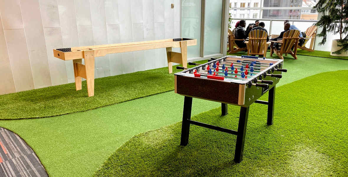 Picture of foosball table and shuffleboard table on green artificial grass