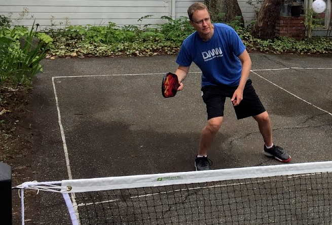 Picture of man playing pickleball. He stands ready to swing at ball in the air