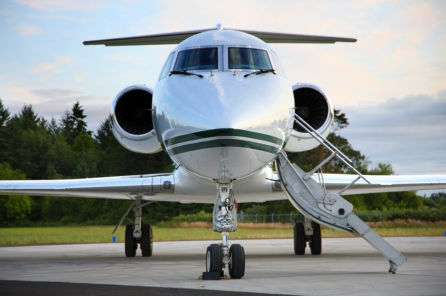 Picture of a private jet sitting on the tarmac with the door open to the right.