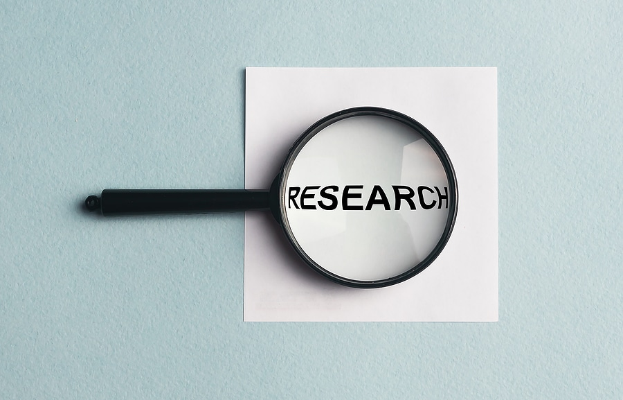 Image of a magnifying glass with the word 'research'
