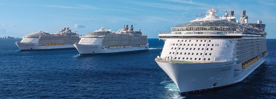 Picture of three Royal Caribbean cruise ships on the ocean with a cityscape in the back