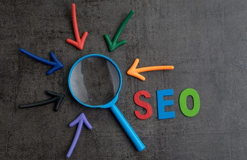 "The word ""SEO"" in red, blue and green on blackboard next to magnifying glass with arrows pointing toward it."