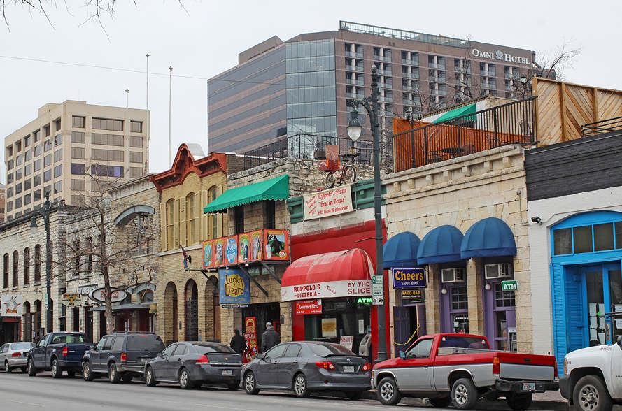A picture of Sixth Street in Austin, Texas, with the Omni Hotel in the background.