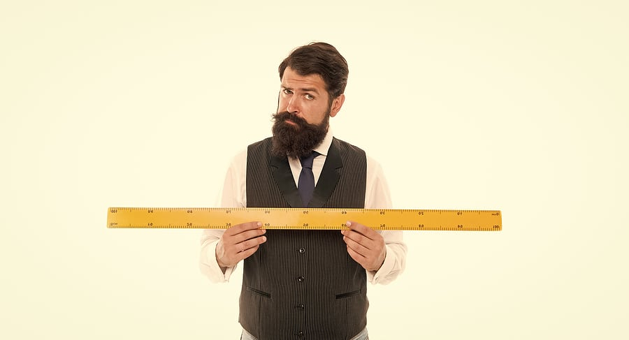 A picture of a bearded man holding a yard stick