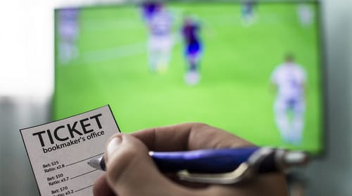 Picture of soccer game on TV in background with person holding betting slip with odds from bookmaker