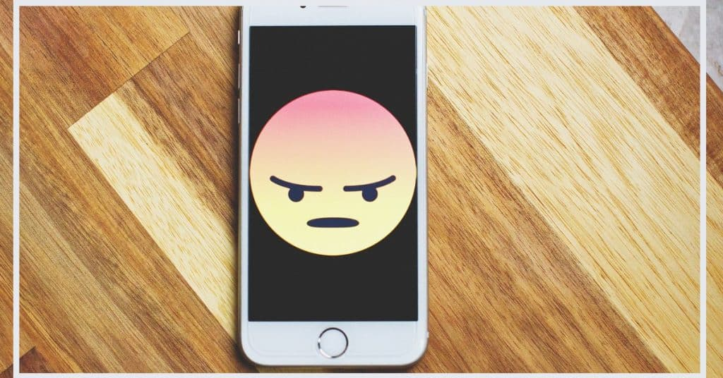 Picture of a mobile phone with a frowning face on it, sitting on a wood background