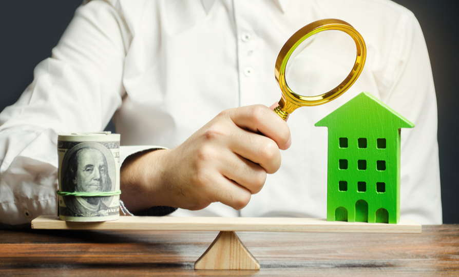 Photo depicting valuation of a home. Person in white shirt with magnifying glass looking at a scale with a bundle of money on one side and a green house on the other.